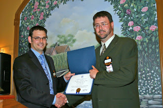 Photo: outgoing President Glenn Maclean congratulated by Robert Lefebvre