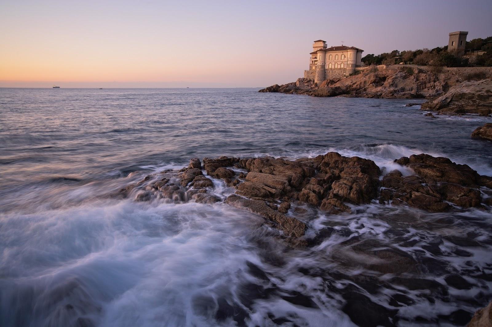 rocks on livorno coast calm sea and coastside building during sunset in tuscany italy