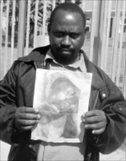 MY BOY: Bhekuyise Mbokazi with a picture of his son's body  after it was found dumped in a dam. Pic. Mhlaba Memela. 18/04/2008. © Sowetan.