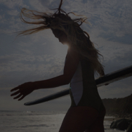 Woman on the beach, walking toward the water while holding a surfboard