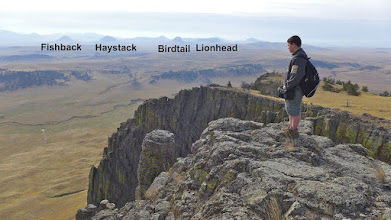 Photo: Jean enjoys a nice view of several smaller buttes (also laccoliths) from Crown Butte. Fishback Butte is where I had a bear encounter in June of 2015. See blog post on bigskywalker.com for more about that hike.