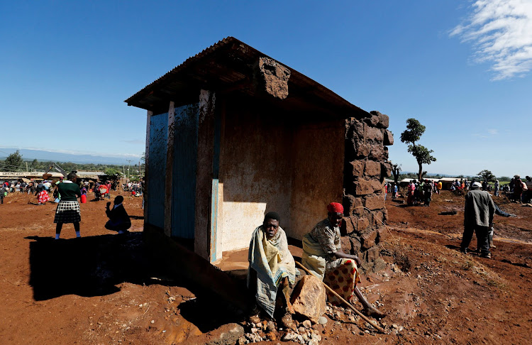 Survivors sit outside their destroyed house after a dam burst, unleashing a torrent over nearby homes, in Solio town near Nakuru, Kenya.