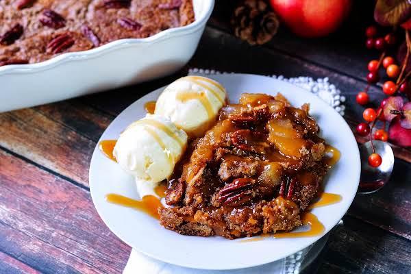 Caramel Apple Pecan Dump Cake On A Plate With Vanilla Ice Cream.