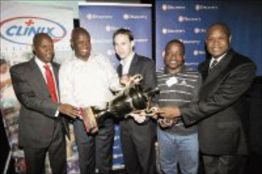 REAL DEAL: From left to right: Khethano Malefane, Phil Mogodi, Hylton Kaliner, Mike Ntombela and Stan Tshabalala display the floating trophy at the launch of the yearly Discovery Walter Sisulu Soccer Challenge in Soweto yesterday. Pic. Veli Nhlapo. 22/11/07. © Sowetan.