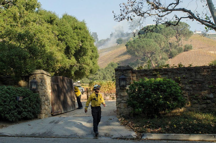 A firefighter walks out of a vineyard owned by Rupert Murdoch damaged by the Skirball fire near the Bel Air neighborhood on the west side of Los Angeles, California, U.S., December 6, 2017.