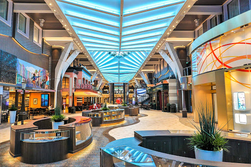 symphony-of-seas-royal-promenade-1.jpg - Follow the checkered floor of the Royal Promenade to see artworks, grab a brew at Copper & Kettle (left) or a bite at Sorrento's (right) on Symphony of the Seas.
