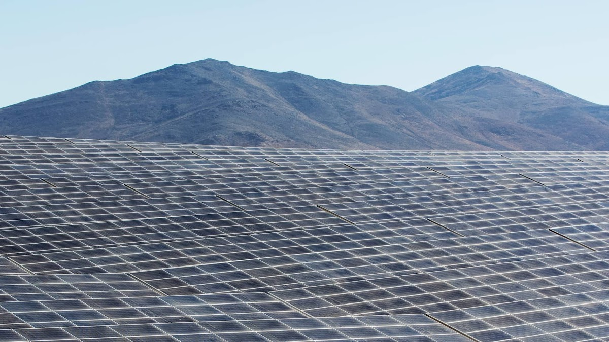 Rows of solar panels aligned in a desert landscape.