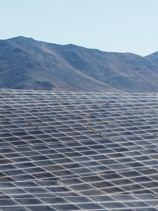 Rows of solar panels aligned in a desert landscape.