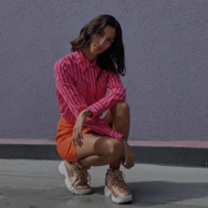 Woman crouched outside, wearing a pink top and orange shorts