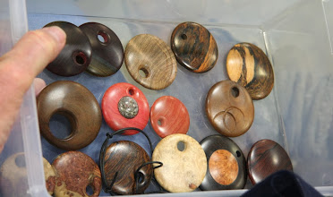 Photo: Here are some sample pendants in a variety of woods.  Note that the off-center holes are chamfered as part of the eccentric turning, not just drilled.  Some pendants are incised with additional eccentric designs.