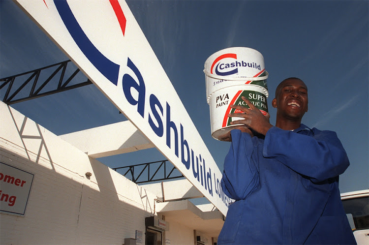 Cashbuild sales assistant Moses Mohlala holds up tins of paint. Picture: SUNDAY TIMES