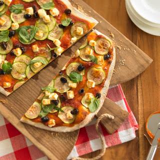 Pizza mit Zucchini, Schafskäse, Oliven und Minze