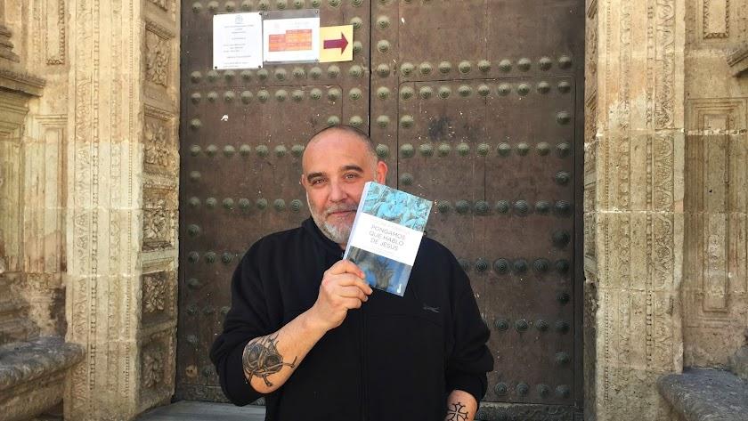Óscar Fábrega muestra un ejemplar de 'Pongamos que hablo de Jesús', en la puerta de la Catedral de Almería.