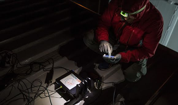 A NetHope field worker wears a headlamp while installing a device-charging station.