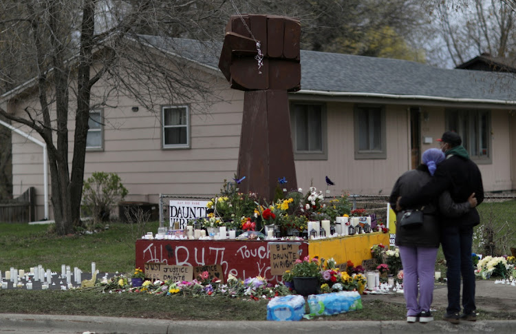 People pay respects to a memorial made from a fist that used to be in George Floyd Square at the site where Daunte Wright was killed by a Brooklyn Center police officer days before in Brooklyn Center, Minnesota on April 14, 2021.