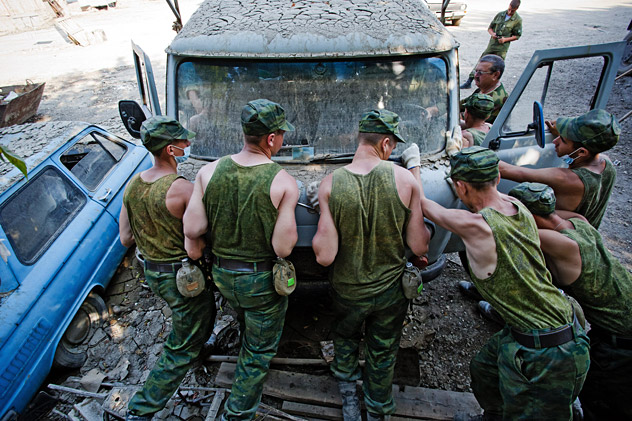 Photo: Members of the military move a damaged vehicle during the clean-up of Krymsk organised after the area was recently hit by severe floods. Source: Ignat Kozlov/RIA Novosti