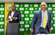 Cricket South Africa (CSA) chief executive Thabang Moroe (L) looks on as SABC chief operating officer Chris Maroleng laughs during a joint media briefing on T20 League at CSA head offices in Johannesburg on September 26, 2018.