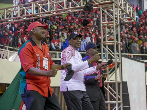 Kanu secretary general NIck Salat dances with President Uhuru Kenyatta and party leader Gideon Moi during its National Delegates Conference at Kasarani stadium in Nairobi, May 6, 2017.