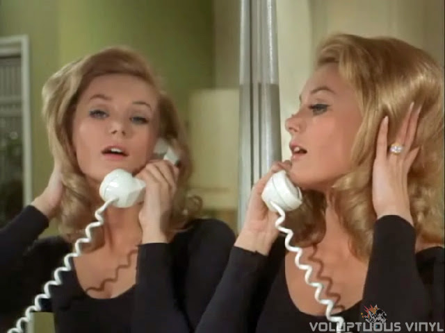 Barbara Bouchet teasing her hair while on the phone in Man from U.N.C.L.E. episode.