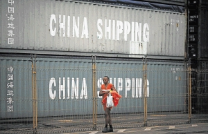 A worker walks past containers of imports from China. PICTURE: REUTERS