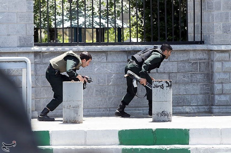 Members of Iranian forces take cover during an attack on the Iranian parliament in central Tehran, Iran, on Wednesday. Picture: TASNIM NEWS AGENCY/HANDOUT VIA REUTERS