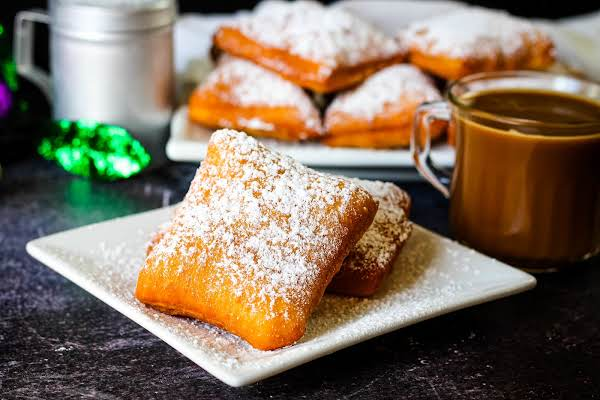Two Authentic Beignets On A Plate With Coffee.