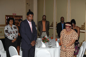 Photo: Participants standing for opening prayer at Dinner, Pegasus Hotel