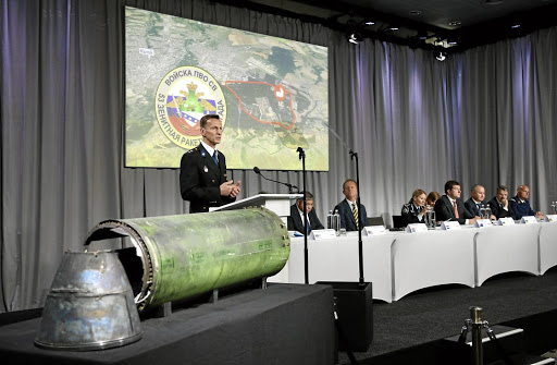 BUK MISSILE: Dutch investigator Wilbert Paulissen, head of the National Crime Squad, next to a damaged missile as he presents interim results in the ongoing investigation of the 2014 MH17 crash, in Bunnik, the Netherlands, on May 24 2018. Picture: REUTERS