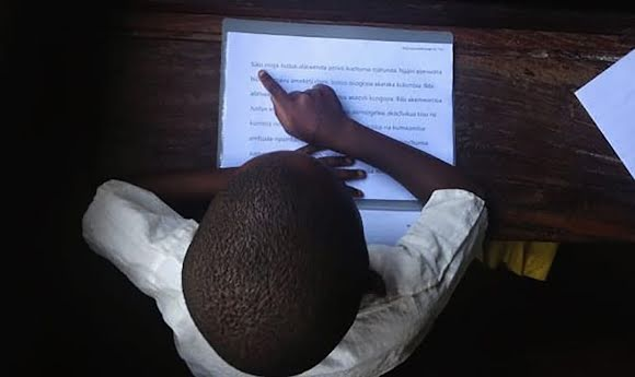 A student practices reading from a piece of paper.