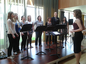 Photo: Sing! performing on the foyer-stage on day five of Summer Music Week, conducted by Steph Richardson.