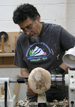Photo: Clif has now unmounted the ball and remounted it in side-grain configuration -- at 90 degrees to it's previous orientation. Note that the previous center mark was very close to the pith. This is some very nice wood. There is no tenon at this point -- he is using the chuck jaws as a large spur drive.
