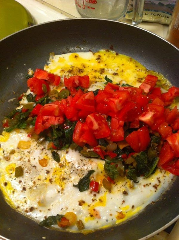 When egg mixture is cooked at the sides of the pan, add shredded cheese,...