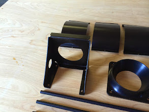 """Photo: This is a folded 0.063"""" bracket for the magnetometer for the G3X.  It will live in the end of the left strake.  I added enough folds that it ended up very stiff.  I could have done this out of 0.040 stock and saved some weight.  To the right is the intake flange for the fuel servo, finally finished and anodized."""