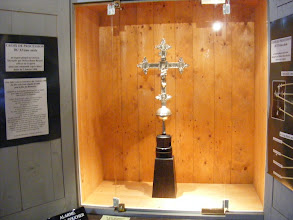 "Photo: This processional cross dates from the 15th century. The order for the fabrication is reprinted on the left, as follows: ""January 2, 1498. Said cross is stipulated for delivery by Palm Sunday. Order for the fabrication of a silver cross for the church and community of Venasque, in the Carpentras diocese. Master Bonet Berard, goldsmith, a resident of Avignon, has promised to said community to fabricate a beautiful cross of pure silver. It will weigh four pounds, and measure two hands in length and about two hands in width. There will be three fleurs de lys on the upper part, and two on the lower part, with a sphere below. There will be on one side, Christ, at the center of the silver cross, with the four evangelists at the extremities of the crucifix. On the other side, the Virgin Mary will be at the center of the cross. Below, the bishop Saint Siffrein will be shown; on the right, there will be a representation of Saint John the Baptist; on the left, a representation of Saint John the Evangelist; below, a representation of Saint Antoine (abbot); these images will be in fine silver. The fabrication price is estimated at 40 florins."" (This appears to be the Italian florin, the dominant coin for trading in Western Europe at this time, which contained about an eighth of an ounce of gold.)"