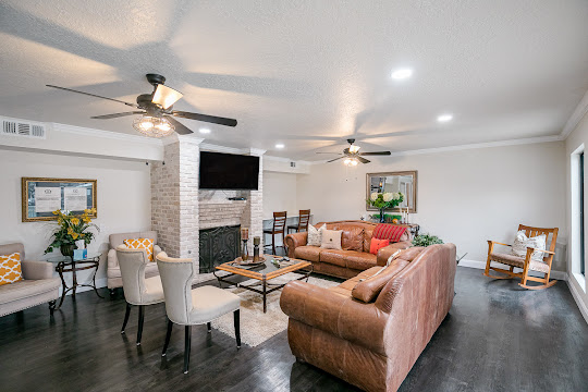 Community clubhouse with wood-inspired flooring, leather couches, fireplace, and TV