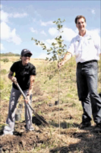 GOING GREEN: Athlete Farwa Mentoor and Wildlands Conservation Trust chief executive officer Andrew Venter plant the first of 13000 trees at the Buffelsdraai Land Refill Site yesterday. 20/05/09. Pic. Thuli Dlamini. © Sowetan.