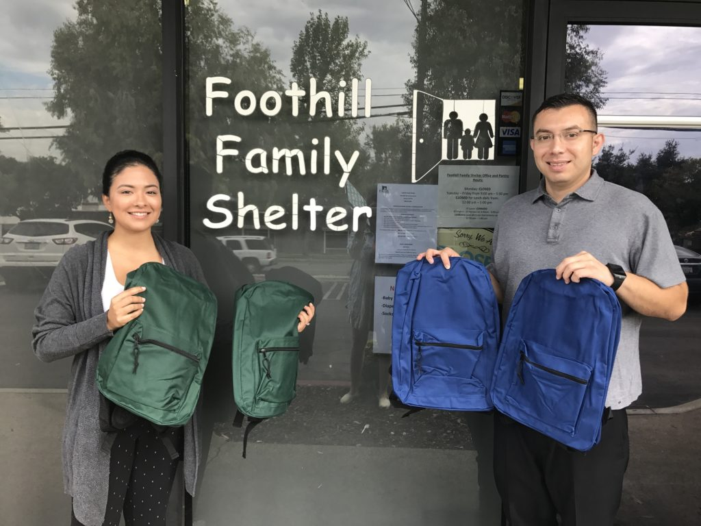 Image of two volunteers holding backpacks in front of a sign that reads Foothill Family Shelter