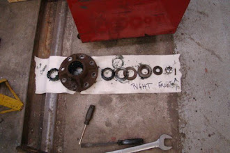 Photo: Right Front Axle parts removed for inspection. Parts are laid out (L-R) in the order they are installed on the axle.  Castle Nut and cotter-pin on far-right. Note that the first item on the left is the roller bearing; which differs from how the left side hub is assembled.  The Operator's Manual doesn't cover this.