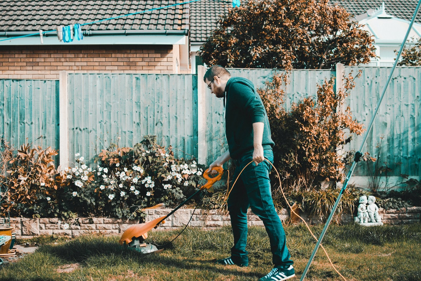 Man using a lawnmower to cut the grass while gardening.