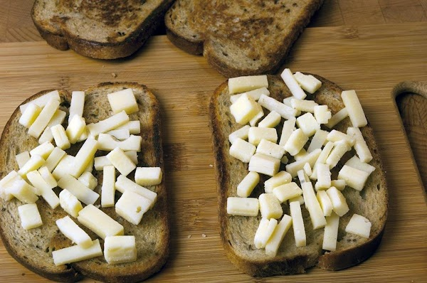 Take half the cheese and spread evenly on two slices of the rye bread,...