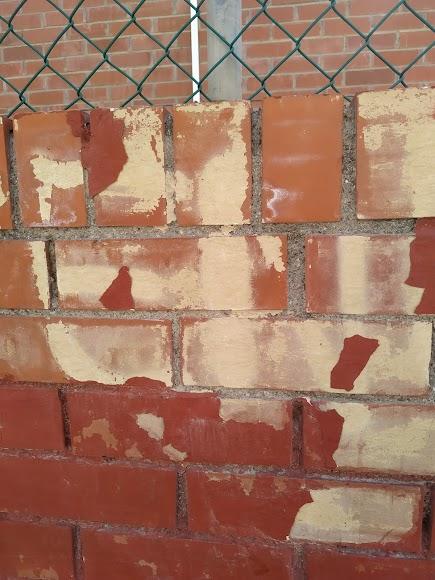Restos de la pintada que aún reaparece en la tapia de la guardería