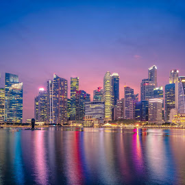 Singapore Skyline and view of skyscrapers on Marina Bay at twili by Nuttawut Uttamaharach - City,  Street & Park  Skylines ( commercial, city, dusk, financial, exterior, skyline, building, east, view, modern, cityscape, hotel, bay, skyscrapers, architecture, tower, sky, famous, business, reflection, wheel, asia, center, night, tree, downtown, singapore, marina, panorama, urban, light, sunset, silhouette, bridge, river, evening, travel, finance, landscape )