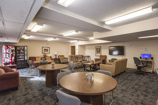 Clubhouse gathering area with plush seating, mounted TV, computer, vending machines