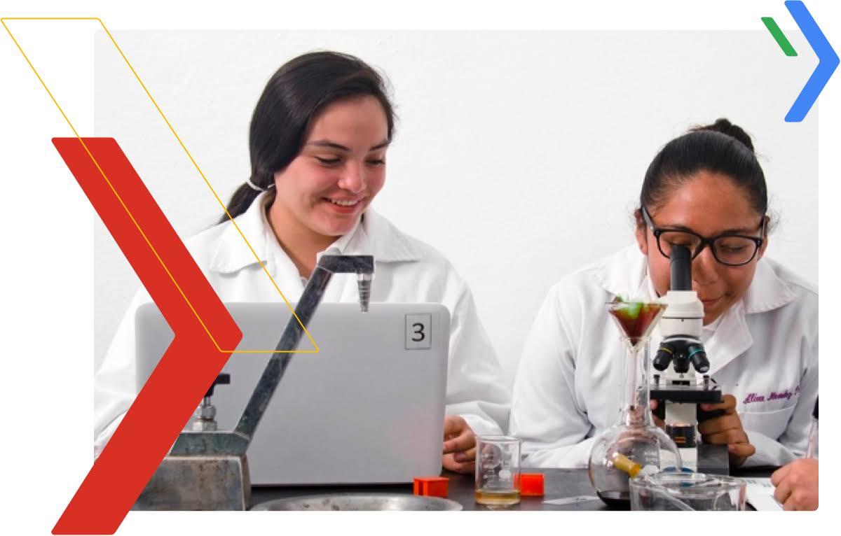 Dos estudiantes mujeres: una mirando por un microscopio y la otra tomando apuntes en su computador