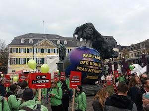 Klimademonstrantinnen in Greenpeace-Jacken, riesige Weltkugel, Luftballons, Transparente: «Klima schützen!» und «Raus aus der Kohle, Frau Merkel!».