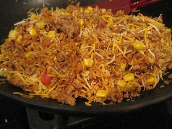 When rice is cooked, add corn, red peppers and cheese. Stir and let cool.