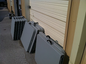 Photo: Grey folding 6 ft tables, marked inside with numbers and folding instructions