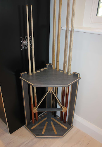 a black cue rack fitting into a corner with pool cues in it