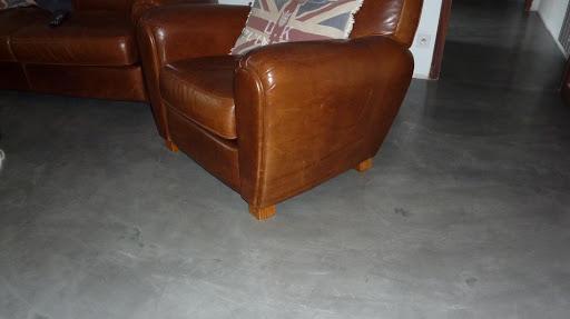 Ce fauteuil Club est mis en valeur grâce au sol en béton ciré qui reflète la lumière