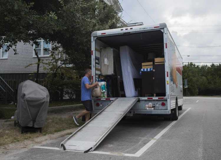 Greg Cook carries belongings to a van as he evacuates days before the arrival of Hurricane Florence at Wrightsville Beach, North Carolina on September 11, 2018.